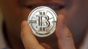 In this April 3, 2013 file photo, Mike Caldwell, a 35-year-old software engineer, holds a 25 Bitcoin token at his shop in Sandy, Utah.  (AP Photo/Rick Bowmer, File)