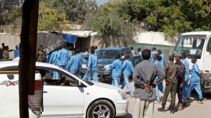 Somali police cadets arrive to help carry away the dead and injured following a suicide bomb attack on a police academy in the capital Mogadishu, Somalia Thursday, Dec. 14, 2017. Islamic extremist suicide bomber disguised as a police officer killed over a dozen people and injured 20 at a police academy in Somalia's capital on Thursday, police said. (AP Photo/Farah Abdi Warsameh)