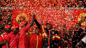 FILE - In this Friday, Aug. 4, 2017 file photo, Kenya's President Uhuru Kenyatta, center, grips the hand of Deputy President William Ruto, 3rd left, as ticker tape falls on them in celebration, at an election rally in Uhuru Park in downtown Nairobi, Kenya. A privacy watchdog said Thursday, Dec. 14, 2017 that Kenya's opposition leader Raila Odinga was targeted by a virulent online campaign created by a Texas-based company during the recent election turmoil. (AP Photo/Ben Curtis, File)