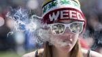 A woman exhales while smoking a joint during the annual 420 marijuana rally on Parliament Hill on Wednesday, April 20, 2016 in Ottawa. THE CANADIAN PRESS/Justin Tang