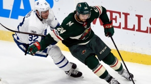 Minnesota Wild defenseman Matt Dumba (24) has the puck against Toronto Maple Leafs left wing Josh Leivo (32) during the second period of an NHL hockey game Thursday, Dec. 14, 2017, in St. Paul, Minn. (AP Photo/Hannah Foslien)