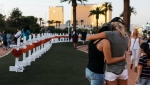 """In this Oct. 5, 2017, file photo, a memorial displaying 58 crosses by Greg Zanis stands at the """"Welcome To Las Vegas Sign"""" in Las Vegas. Each cross has the name of a victim killed during the mass shooting at the Route 91 Harvest country music festival this past Sunday, Oct. 1. A plan that will be used to divide donations to victims of the Las Vegas mass shooting includes a provision to assist those who sought medical attention but weren't hospitalized. The committee overseeing the distribution of more than $22 million released the final plan Friday, Dec. 15. (Mikayla Whitmore/Las Vegas Sun via AP, File)"""