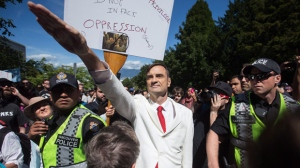 Brian Ruhe gives a Nazi salute as police officers move in for his protection as alt-right protesters and anti-racism protesters take part in rallies at City Hall in Vancouver, B.C., on Saturday, August 19, 2017. THE CANADIAN PRESS/Darryl Dyck