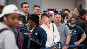 People wait in line to rebook flights at Hartfield-Jackson Atlanta International Airport , Monday, Dec. 18, 2017, in Atlanta. (AP Photo John Amis)
