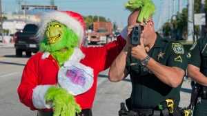 In this Tuesday, Dec. 12, 2017, photo provided by the Florida Keys News Bureau, Monroe County Sheriff's Office Col. Lou Caputo, left, has some fun with Deputy Willie Guerra as he aims a radar speed gun in a school zone on the Florida Keys Overseas Highway in Marathon, Fla. (Andy Newman/Florida Keys News Bureau via AP)