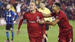 Toronto FC midfielder Benoit Cheyrou (8) celebrates his goal against the Montreal Impact with teammate Justin Morrow (2) during extra time of MLS Eastern Conference playoff soccer final action in Toronto on Wednesday, November 30, 2016. THE CANADIAN PRESS/Nathan Denette