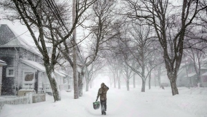 A man walks down the middle of Agricola Street in Halifax as a major winter storm blasts the Maritimes on Monday, Feb. 13, 2017. (THE CANADIAN PRESS/Darren Calabrese)