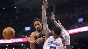 Toronto Raptors guard DeMar DeRozan (left) passes the ball while under pressure from Philadelphia 76ers Amir Johnson during second half NBA basketball action in Toronto on Saturday, December 23, 2017. THE CANADIAN PRESS/Chris Young