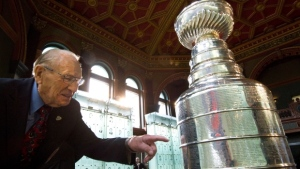 "Hockey Hall of Famer Johnny Bower looks for his names on the Stanley Cup after The Hockey Hall of Fame officially unveiled the "" Esso Great Wall"" as home to the Stanley Cup in Toronto on Friday, March. 9, 2012. (THE CANADIAN PRESS/Nathan Denette)"