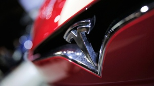 This Friday, Sept. 30, 2016, file photo shows the logo of the Tesla Model S on display at the Paris Auto Show in Paris. (AP Photo/Christophe Ena, File)