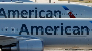 In this Monday, Nov. 6, 2017, file photo, a pair of American Airlines jets are parked on the airport apron at Miami International Airport in Miami. (AP Photo/Wilfredo Lee, File)