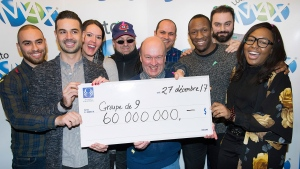 Lotto Max winners Julie Beland, Haidar Abi Haidar, Robert Macri, Diane Dorele Fossouo Djuidje, Nathaniel Thomas, Darius Hozhabr Zandi, Peter Jewett, Randolph Dandan and Enzo Scattone hold up a cheque for $60,000,000 in Montreal, Wednesday, December 27, 2017, after winning the jackpot on Friday, December 22, in Montreal. THE CANADIAN PRESS/Graham Hughes