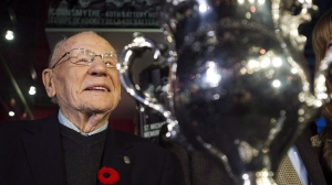 Canadian Second World War veteran and hockey hall of fame inductee Johnny Bower is seen next to the Memorial Cup as he takes part in a new exhibit dedicated to First World War and Second World War veterans at the Hockey Hall of Fame in Toronto on November 10, 2014.  THE CANADIAN PRESS/Nathan Denette