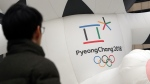 In this Dec. 29, 2017, photo, a man walks by the official emblem of the 2018 Pyeongchang Olympic Winter Games, in downtown Seoul, South Korea. (AP Photo/Lee Jin-man)