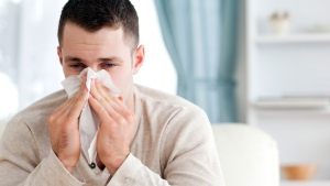 A man with the common cold sneezes into a tissue. (wavebreakmedia ltd/shutterstock.com)