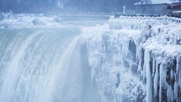 Visitors take photographs at the brink of the Horseshoe Falls in Niagara Falls, Ont., as cold weather continues through much of the province, Tuesday, January 2, 2018. THE CANADIAN PRESS/Aaron Lynett