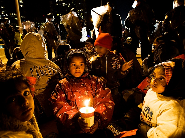 Children sit as police stand in front of Tamil demonstrators after the protestors successfully blocked the Gardiner Expressway in Toronto on Sunday, May 10, 2009. (THE CANADIAN PRESS/Nathan Denette)