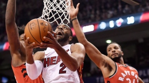Miami Heat guard Wayne Ellington (2) goes up for a shot past Toronto Raptors forward Norman Powell (24) and centre Lucas Nogueira during second half NBA basketball action in Toronto on Tuesday, January 9, 2018. THE CANADIAN PRESS/Nathan Denette