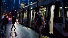 Commuters exit a streetcar at a TTC stop at Bathurst and King St. during the second day of the King Street Transit Pilot between Bathurst and Jarvis Street on Monday, November 13, 2017. THE CANADIAN PRESS/Christopher Katsarov
