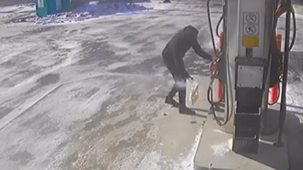 A suspect is seen placing a flaming bag at the foot of a gas pump in Scarborough on Jan. 13, 2018. (Toronto Police)