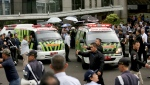 Ambulances carrying injured persons leave the Jakarta Stock Exchange tower in Jakarta, Indonesia, Monday, Jan. 15, 2018. A mezzanine floor inside the tower collapsed on Monday, injuring dozens of people and forcing a chaotic evacuation. (AP Photo/Tatan Syuflana)