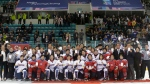 FILE - In this April 6, 2017, file photo, women's ice hockey players of South Korea, in white, and North Korea, in red, pose for a photo with International Ice Hockey Federation officials after their Ice Hockey Women's World Championship Division II Group A game in Gangneung, South Korea. North and South Korea agreed on Monday, Jan. 15, 2018, in principle to field a joint women's ice hockey team during next month's Olympics in South Korea, and relayed their position to the International Olympic Committee. (AP Photo/Ahn Young-joon, File)