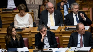 Greek Labour Minister Effie Achtsioglou, left, Greek Finance Minister Euclid Tsakalotos, center, and Minister of Energy, Giorgos Stathakis, right, listen to Greek Prime Minister Alexis Tsipras' speech during a Parliament session before the vote on a new batch of reforms, including measures that would make it harder for labor unions to call strikes, in Athens, on Monday, Jan. 15, 2018. (AP Photo/Petros Giannakouris)