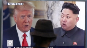 "FILE - In this Aug. 10, 2017, file photo, a man watches a television screen showing U.S. President Donald Trump and North Korean leader Kim Jong Un during a news program at the Seoul Train Station in Seoul, South Korea. North Korea's state-run media say U.S. President Donald Trump's tweet about having a bigger nuclear button than Kim Jong Un's is the ""spasm of a lunatic."" (AP Photo/Ahn Young-joon, File)"