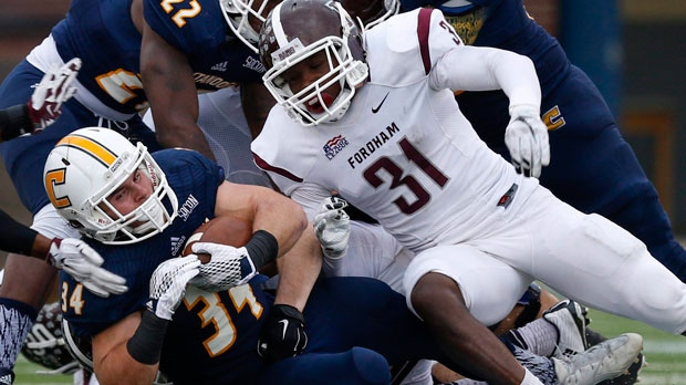 Chattanooga running back Derrick Craine, left, falls to the ground ahead of Fordham defensive back Caleb Ham during the second half in a first round game in the NCAA college Football Championship Subdivision playoff at Finley Stadium, Saturday, Nov. 28, 2015, in Chattanooga, Tenn. (Doug Strickland/Chattanooga Times Free Press via AP)