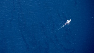 In this Jan. 15, 2018, aerial photo released by China's Xinhua News Agency, a boat moves through an oil slick on the surface of the East China Sea left by oil leaking from the sunken Iranian tanker ship Sanchi. Several oil slicks have been found in waters around a sunken Iranian tanker ship in the East China Sea in a spill that is growing and whose potentially major impact on the marine environment is still being assessed. (Liu Shiping/Xinhua via AP)