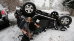 Julius Rigole retrieves belongings from his overturned Jeep after an accident on a snow covered road in Richmond, Va., Wednesday, Jan. 17, 2018. A winter storm is making it's way through Virginia. (AP Photo/Steve Helber)