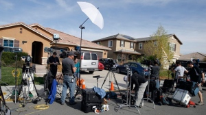 Members of the media work outside a home Tuesday, Jan. 16, 2018, where police arrested a couple on Sunday accused of holding 13 children captive, in Perris, Calif. Authorities said an emaciated teenager led deputies to the California home where her 12 brothers and sisters were locked up in filthy conditions, with some of them malnourished and chained to beds. (AP Photo/Alex Gallardo)
