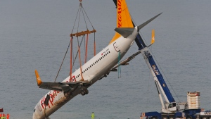 A crane lifts a Boeing 737-800 of Turkey's Pegasus Airlines from a slope in Trabzon, Turkey, Thursday, Jan. 18, 2018. Turkish authorities lifted the passenger plane that skidded off a runway in northern Turkey and stopped on the side of a slope meters away from the Black Sea late Saturday. All passengers and crew were evacuated and no one was injured.(AP Photo/Lefteris Pitarakis)