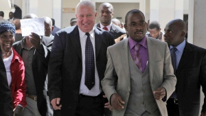 In this May, 10, 2010, file photo, Roy Bennett, center left, leaves the High Court in Harare, Zimbabwe, after he was acquitted of terrorism charges. New Mexico State Police said Thursday, Jan. 18 2018, that Zimbabwean opposition leader Roy Bennett died in helicopter crash. The crash on Wednesday, Jan. 17, carrying Bennett and five others went down in a mountainous rural area of northern New Mexico. (AP Photo/Tsvangirayi Mukwazhi, File)