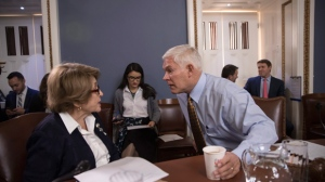 House Rules Committee Chairman Pete Sessions, R-Texas, center, confers with Rep. Louise Slaughter, D-N.Y., the top Democrat, as the panel meets on Capitol Hill in Washington, Thursday, Dec. 21, 2017. With a government shutdown clock ticking toward a midnight Friday deadline, House Republican leaders struggled on Wednesday to unite the GOP rank and file behind a must-pass temporary spending bill. (AP Photo/J. Scott Applewhite)