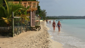 In this Sept. 14, 2014 photo, sunbathers walk along resort-lined crescent beach in Negril in western Jamaica. Canadian sun seekers in Jamaica are being urged to ``exercise a high degree of caution'' following a spate of violent crime in the popular winter getaway. THE CANADIAN PRESS/AP-David McFadden