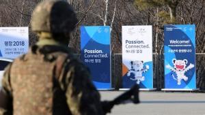 Posters showing the 2018 Pyeongchang Winter Olympic mascot are displayed as a South Korean army soldier stands guard at the Unification Observation post in Goseong, near the border with North Korea, South Korea, Friday, Jan. 19, 2018. (AP Photo/Ahn Young-joon)