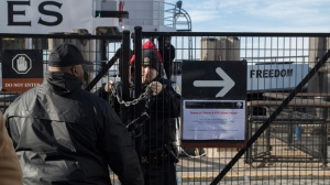"A United States Park Police officer, center, locks a gate leading to a Statue of Liberty ferry, Saturday, Jan. 20, 2018, in New York. The National Park Service announced that the Statue of Liberty and Ellis Island would be closed Saturday ""due to a lapse in appropriations."" Late Friday, the Senate failed to approve legislation to keep the government from shutting down after the midnight deadline. (AP Photo/Mary Altaffer)"