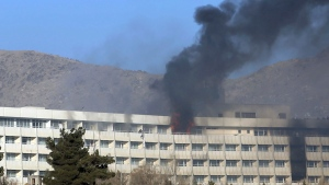 Men try to escape from a balcony of the Intercontinental Hotel after an attack in Kabul, Afghanistan, Sunday, Jan. 21, 2018. Gunmen stormed the hotel and sett off a 12-hour gun battle with security forces that continued into Sunday morning, as frantic guests tried to escape from fourth and fifth-floor windows. (AP Photo/Rahmat Gul)
