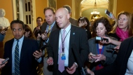 Marc Short, White House director for legislative affairs, answers to reporters as he walks to the office of Senate Majority Leader Mitch McConnell, R-Ky., as the second day of the federal shutdown drags on at Capitol, Sunday, Jan. 21, 2018, in Washington. (AP Photo/Jose Luis Magana)