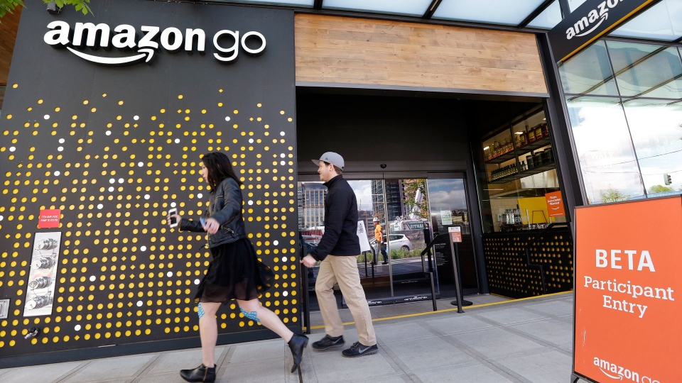 In this Thursday, April 27, 2017, file photo, people walk past an Amazon Go store in Seattle. More than a year after it introduced the concept, Amazon is opening its artificial intelligence-powered Amazon Go store in downtown Seattle on Monday, Jan. 22, 2018. (AP Photo/Elaine Thompson, File)