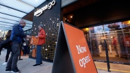 A customer is handed a complimentary shopping bag as he heads into an Amazon Go store, Monday, Jan. 22, 2018, in Seattle. More than a year after it introduced the concept, Amazon opened its artificial intelligence-powered Amazon Go store in downtown Seattle on Monday. AP Photo/Elaine Thompson)