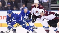 Toronto Maple Leafs defenceman Jake Gardiner (51) battles for control of the puck with Colorado Avalanche right wing Nail Yakupov (64) during third period NHL hockey action in Toronto on Monday, January 22, 2018. THE CANADIAN PRESS/Nathan Denette