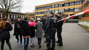 Police secures the schoolyard of a school in Luenen, Germany Tuesday, Jan. 23, 2018.Police say a student has been killed by a fellow pupil at a school in western Germany. Dortmund police said the incident happened Tuesday morning at a school in the nearby town of Luenen. Police said a minor has been arrested and investigations into the killing are ongoing. (AP Photo/Martin Meissner)