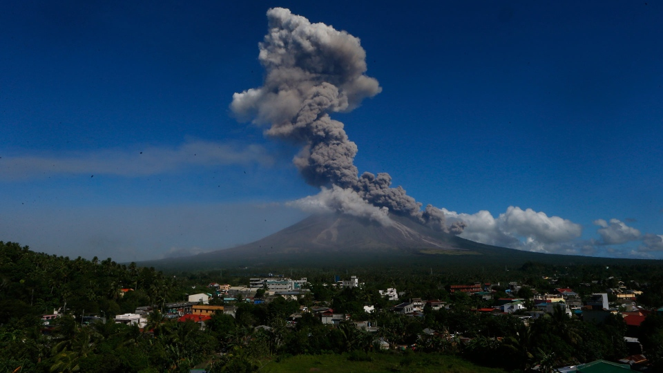 Mayon volcano spews ash as it erupts anew Tuesday, Jan. 23, 2018 as seen from Legazpi city, Albay province, southeast of Manila, Philippines. The Philippines' most active volcano ejected a huge column of lava fragments, ash and smoke in another thunderous explosion at dawn Tuesday, sending thousands of villagers back to evacuation centers and prompting a warning that a violent eruption may be imminent. (AP Photo/Bullit Marquez)