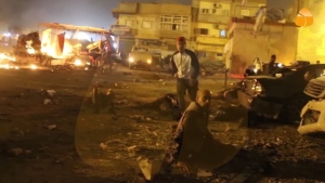 This grab taken from Al-Hadath Channel video on Tuesday Jan. 23, 2018, shows debris at the site of an explosion in Benghazi, Libya. Two consecutive car bombs detonated near a mosque in the Libyan city of Benghazi on Tuesday, killing at least nine people and injuring dozens more. (Al-Hadath Channel via AP)