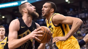 Toronto Raptors centre Jonas Valanciunas (17) goes to the net against Utah Jazz centre Rudy Gobert (27) during second half NBA basketball action in Toronto on Friday, January 26, 2018. THE CANADIAN PRESS/Frank Gunn