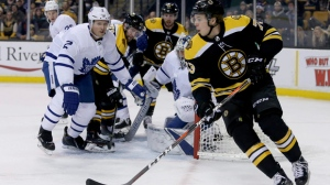 Boston Bruins defenseman Charlie McAvoy (73) looks to pass into a crowded goal during the second period of an NHL hockey game against the Toronto Maple Leafs, Saturday, Feb. 3, 2018, in Boston. (AP Photo/Mary Schwalm)