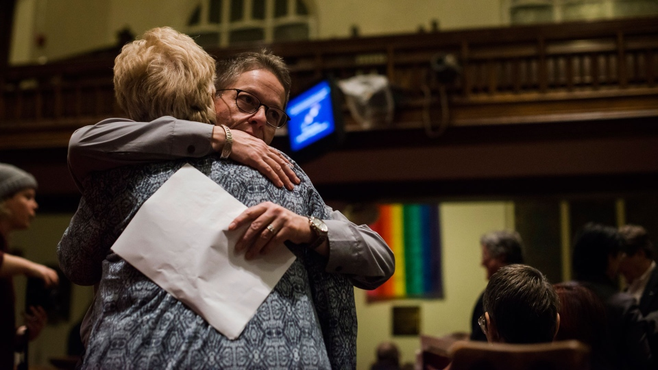 Community members embrace during a vigil hosted by the Metropolitan Community Church of Toronto, in Toronto on Sunday, February 4, 2018. A downtown Toronto neighbourhood came together to mourn the deaths of several men in the LGBTQ community at the hands of an alleged serial killer. THE CANADIAN PRESS/Christopher Katsarov