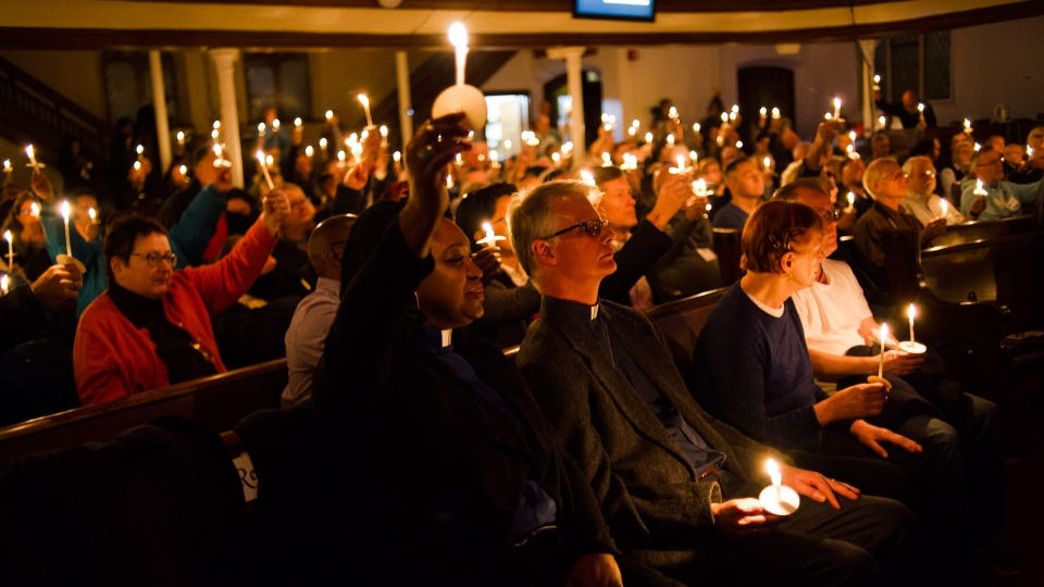 Community members and dignitaries hold lit candles in the air during a vigil hosted by the Metropolitan Community Church of Toronto, in Toronto on Sunday, February 4, 2018. A downtown Toronto neighbourhood came together to mourn the deaths of several men in the LGBTQ community at the hands of an alleged serial killer.THE CANADIAN PRESS/Christopher Katsarov